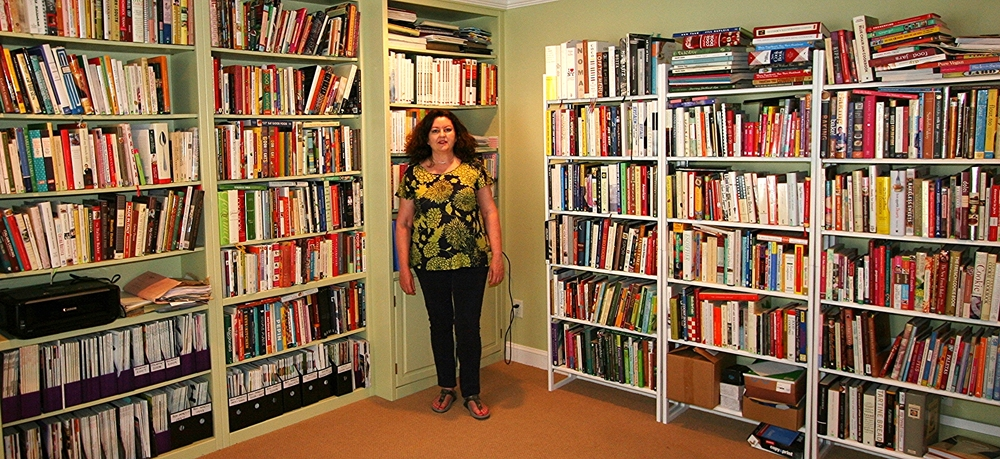 Jane Kelly and a few of her 700+ cookbooks. (photos courtesy of Eat Your Books)