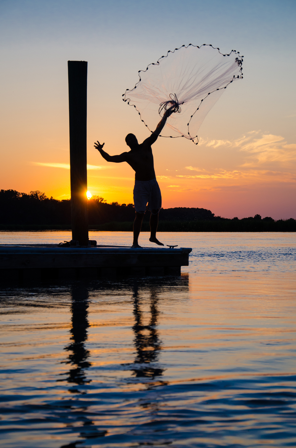 Silhouette of man throwing a cast net at sunset on Edisto Island.