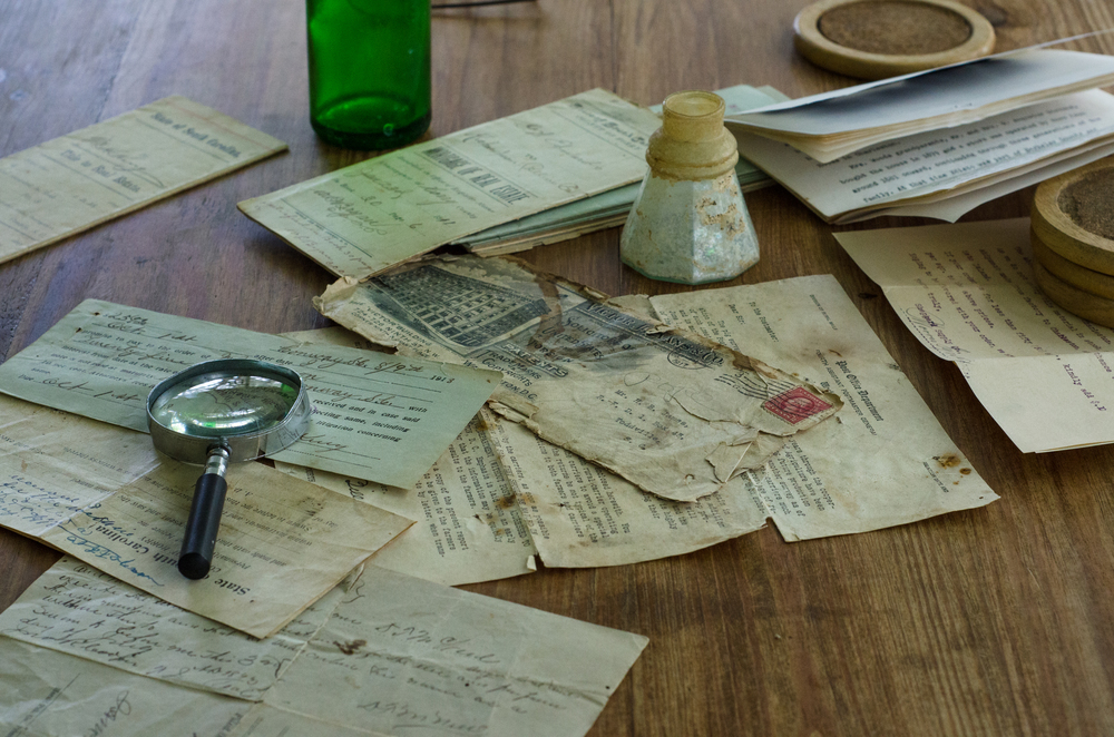 Old letters, notes and deeds with a magnifying glass.