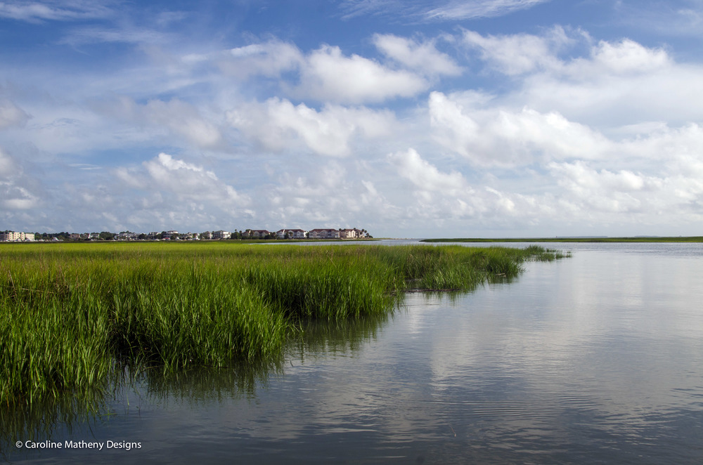 A winding creek, marsh grass and a view of Edisto Island in the distance.