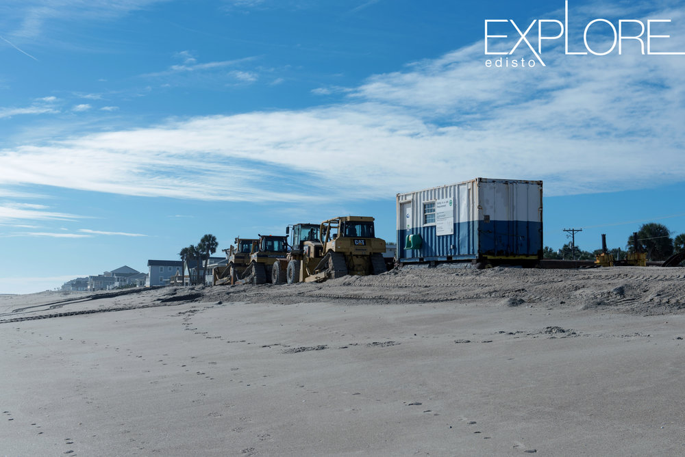 Container and tractors on the beach.
