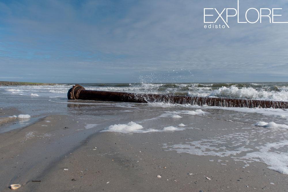 Water splashing against pipe in ocean for beach nourishment.