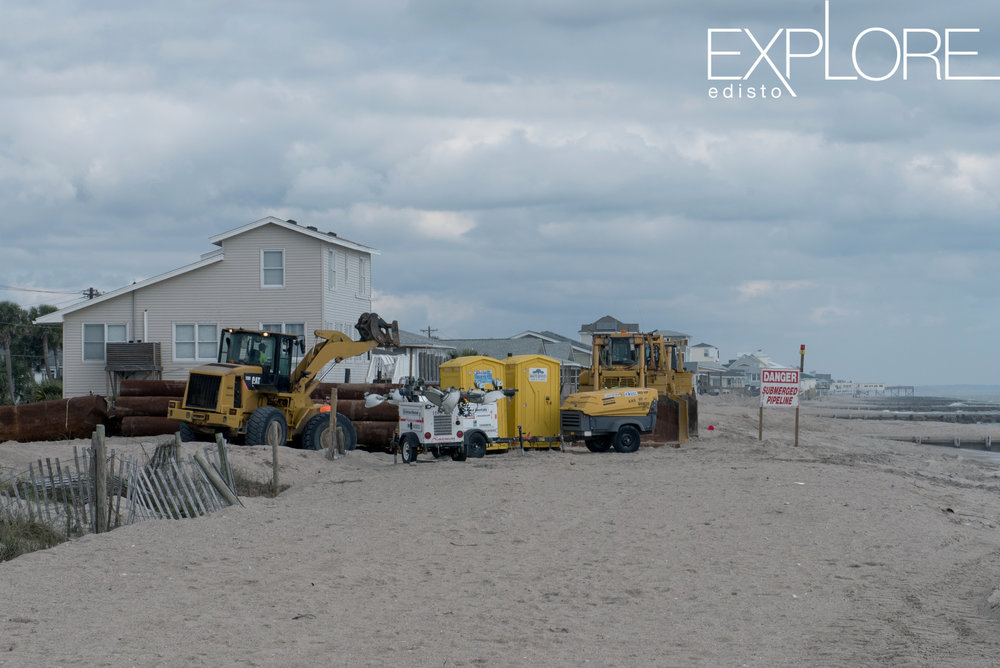 Portable toilets next to tractors on the beach.