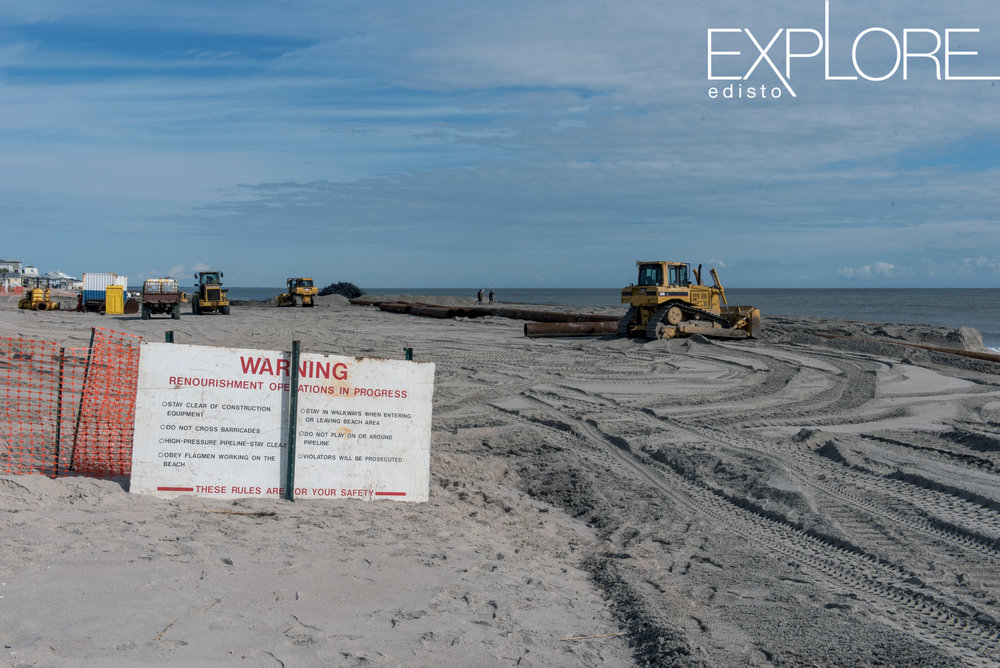 Warning sign in front of working area with tractors on the beach.