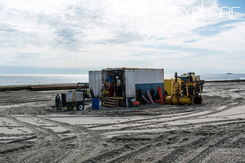 Men at work inside a container on the beach during beach renourishment.