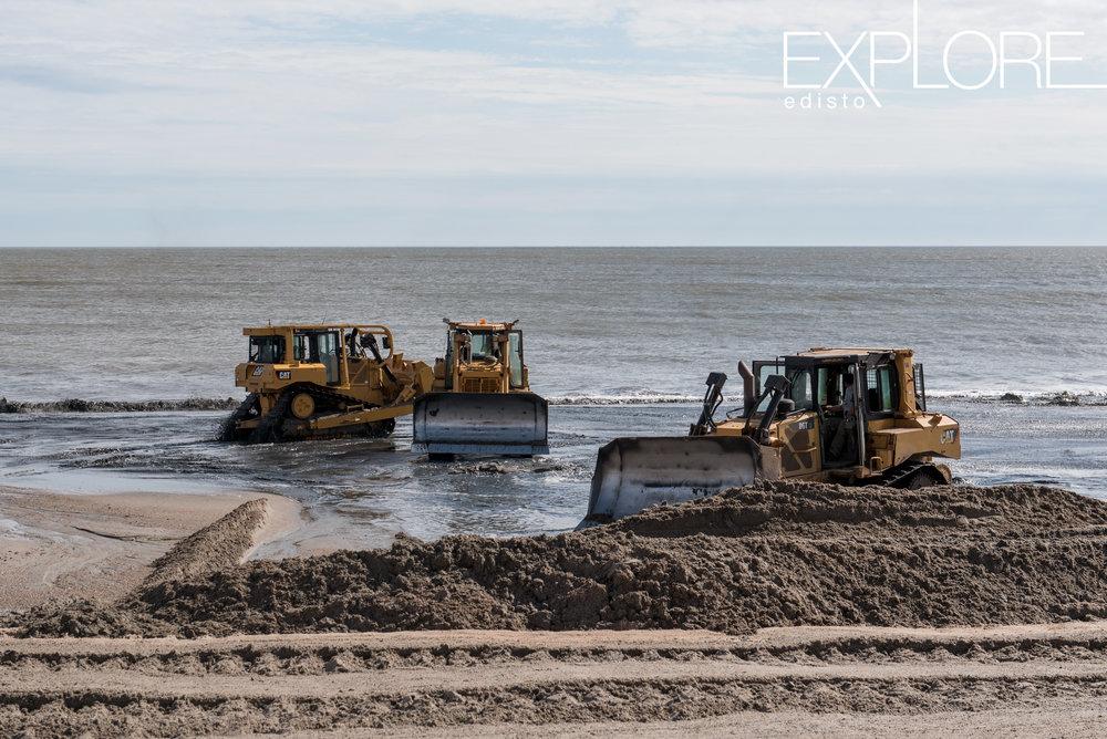 Three tractors working on pushing sand onto the beach during beach nourishment.