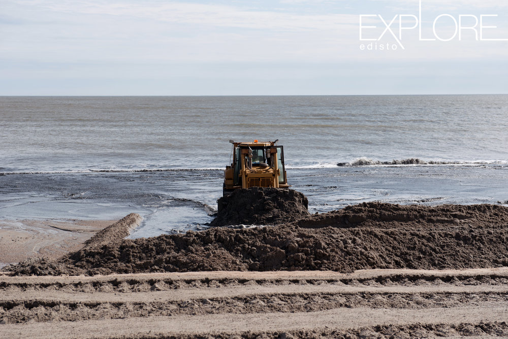 A lone tractor hard at work pushing sand onto the beach during beach nourishment.