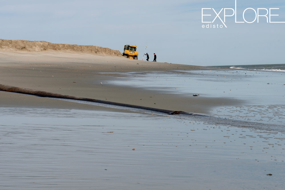 Pipe running into ocean with two men and a tractor in the distance on the beach.