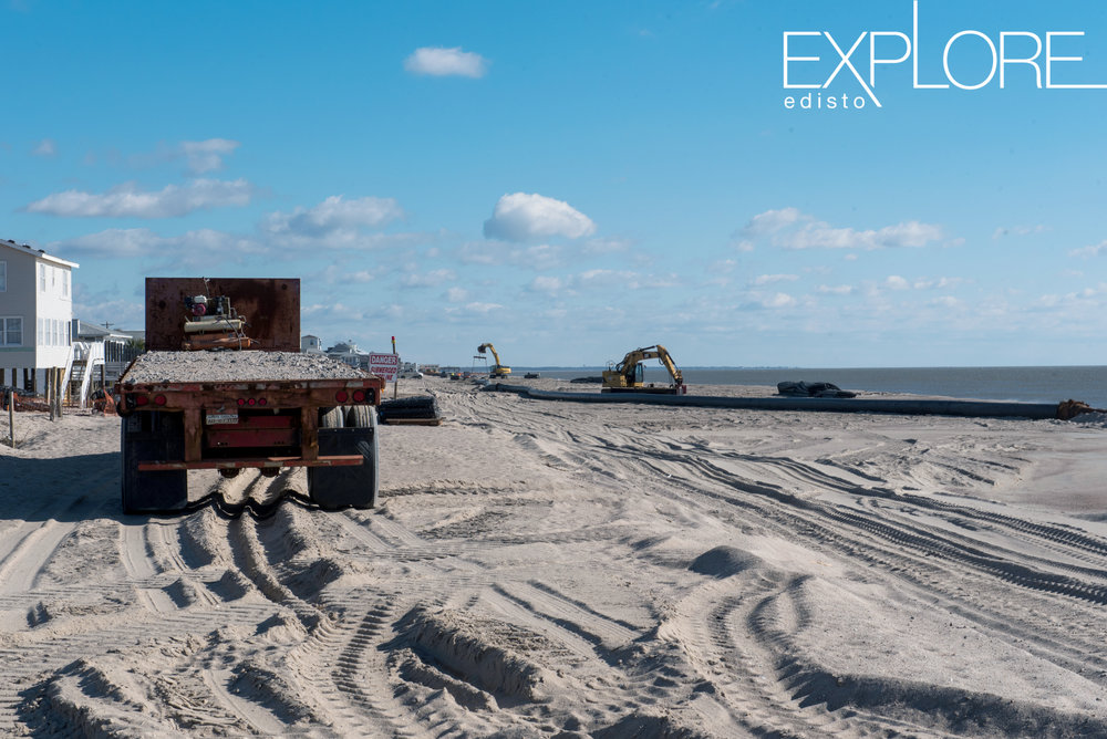 Flatbed truck on beach with tractors in the distance.