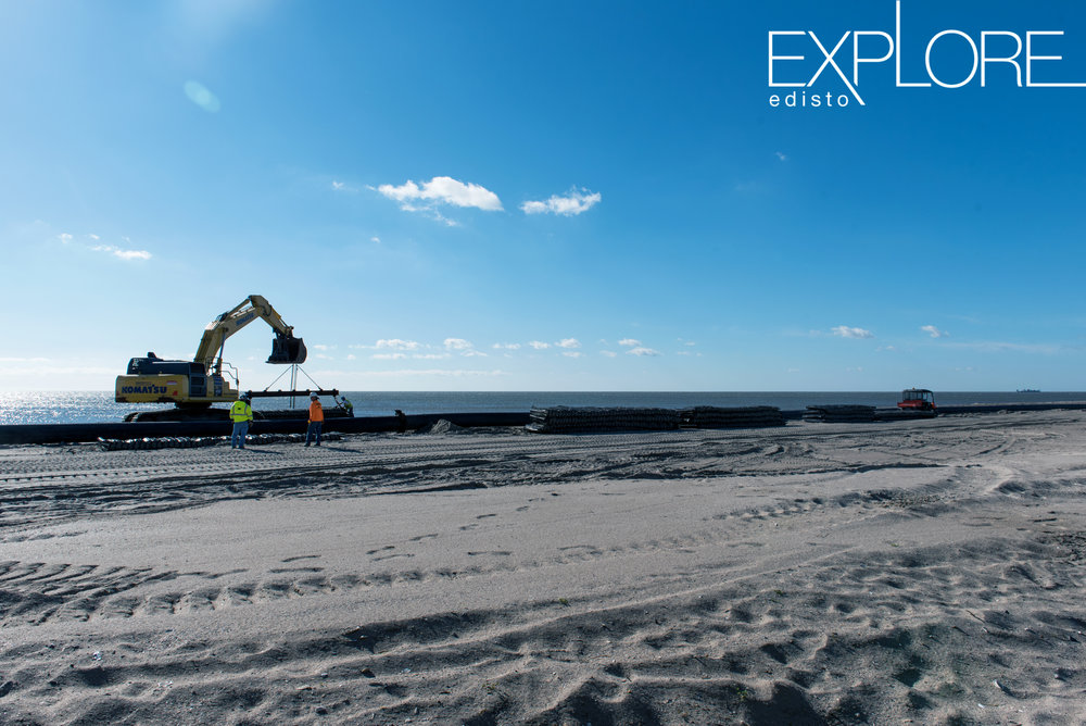 Crane moving rocks on the beach.