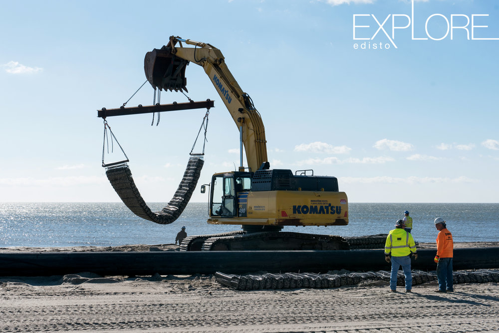 Crane moving rocks on the beach with workers wearing hard hats and neon yellow and orange.