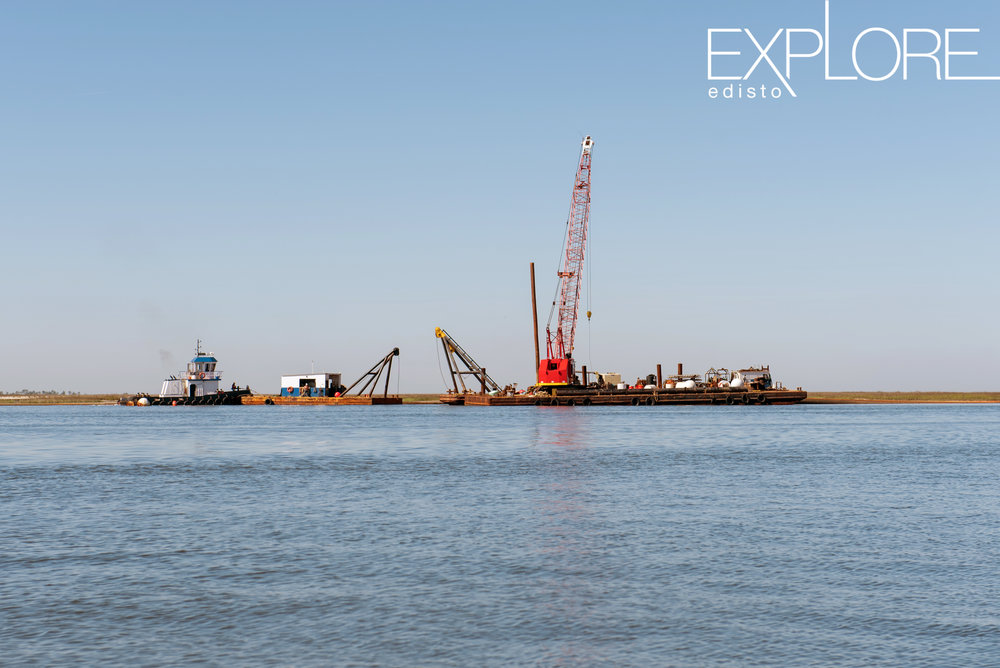 Barge, freight and crane in the distance on the water.