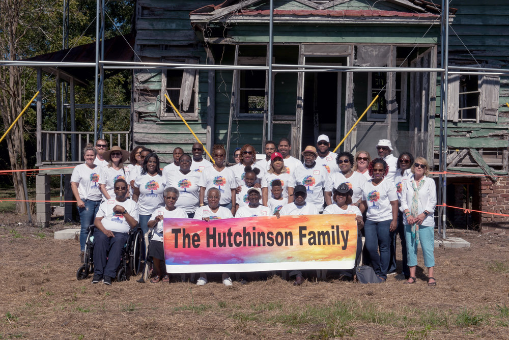 The Hutchinson Family poses together holding a sign in front of the old green Hutchinson House on Edisto Island, SC.