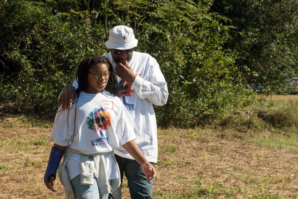 Man and girl walk through yard wearing Hutchinson House Family Reunion t-shirts.