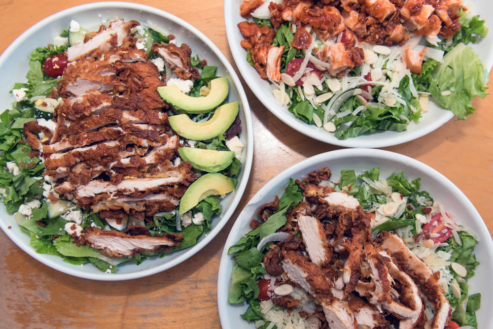 (Clockwise)The Big Salad with Fried Chicken, The Buffalo Chicken Salad with Hot Wing Sauce, The Buffalo Salad with the sauce on the side.