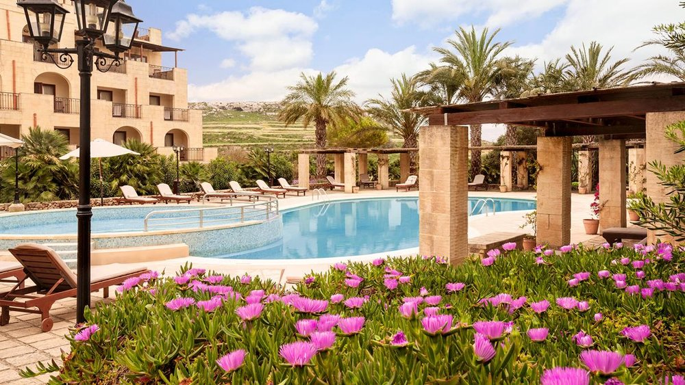 kempinski pool with flowers and loungers.jpg