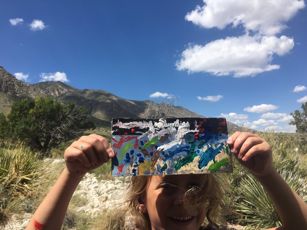 Another young artist (4yo) holding up her expressive response to the landscape on a recycled map!