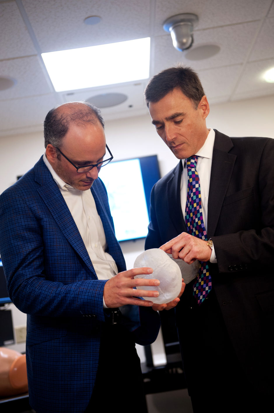 Dr. Peter Weinstock, left, and Dr. John G. Meara examining a 3-D model of Violet's skull. (Photo credit: Katherine C. Cohen/Boston Children's Hospital)