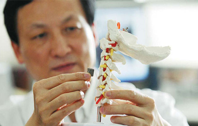 Photo Credit: Peking University   Doctors from the Peking University Third Hospital in China has just performed what is perhaps one of the biggest 3D implants to date. A 12-year-old boy suffering from spinal cord cancer just received a 3D-printed vertebra implant.  The implant was made from titanium powder like other orthopedic implants but, according to Engadget, is said to be safer and longer-lasting than others of its kind. Another major benefit is that it is shaped after the original vertebra, so it doesn't require cement to screws as reinforcements. Instead, it has holes to allow for the natural bone to grow through so that the implant eventually becomes a permanent part of the spine. This is likely to also help make the healing process a bit faster.  The patient will have to wear gear to keep his head and neck still for three months following the surgery. However, it is believed that the process will actually take much longer before doctors are able to see how the implant holds up in the real w