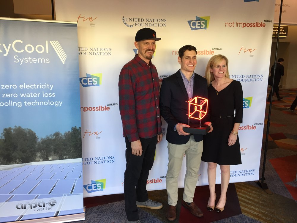 Mick Ebeling (Founder and CEO, Not Impossible) and Fiserv's Katherine Beacham, present the inaugural Not Impossible Award to Taylor Steindel of SkyCool Systems.