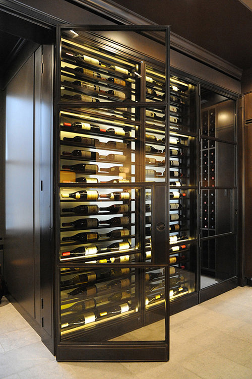 Bronze framed wine room with custom hinges and door hardware, designed to fold open flush.