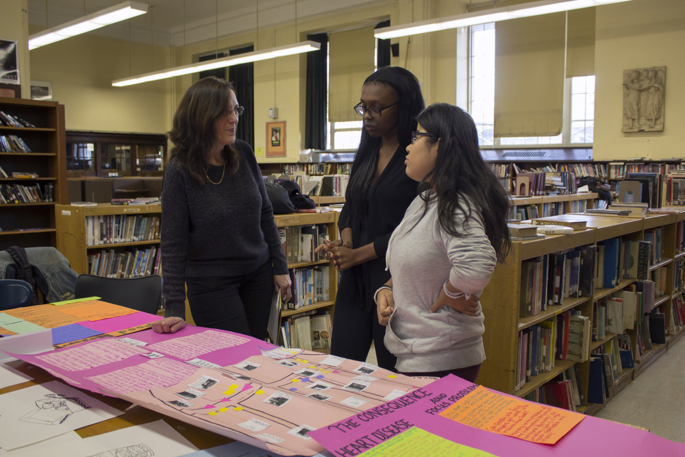 Two students explain their research on hormone imbalance and unhealthy eating to their Assistant Principal.