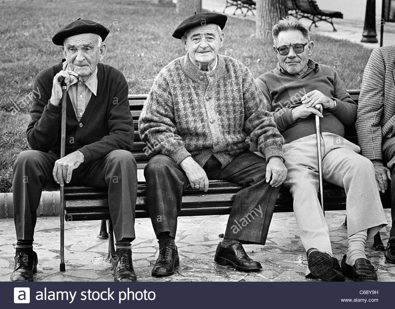 three-old-men-two-with-traditional-basque-berets-sit-on-a-park-bench-C68Y9H