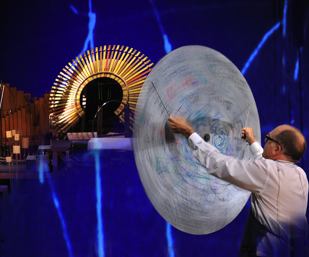 Pictured: Steven Schick playing The Big Disc in the Paul Dresher Ensemble production of Schick Machine. Photo courtesy of the Paul Dresher Ensemble, design by 8 Point 2 Design.