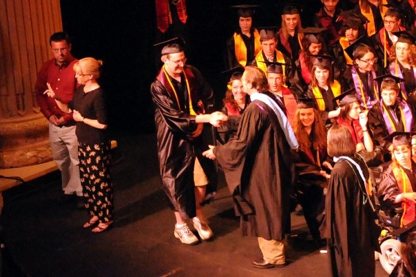 Aaron receiving his diploma and shaking hands with Jon Ketler at graduation