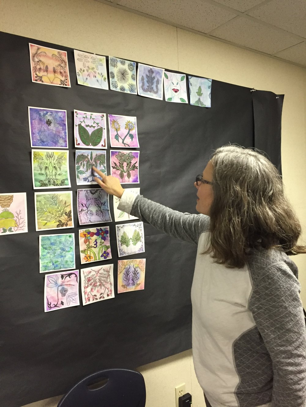 Mary Mann, showing off the paintings based on foliage found during one of the walks in Point Defiance.