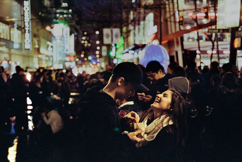 A candid moment of a young couple while waiting for the lighting of the Christmas tree in Vancouver.