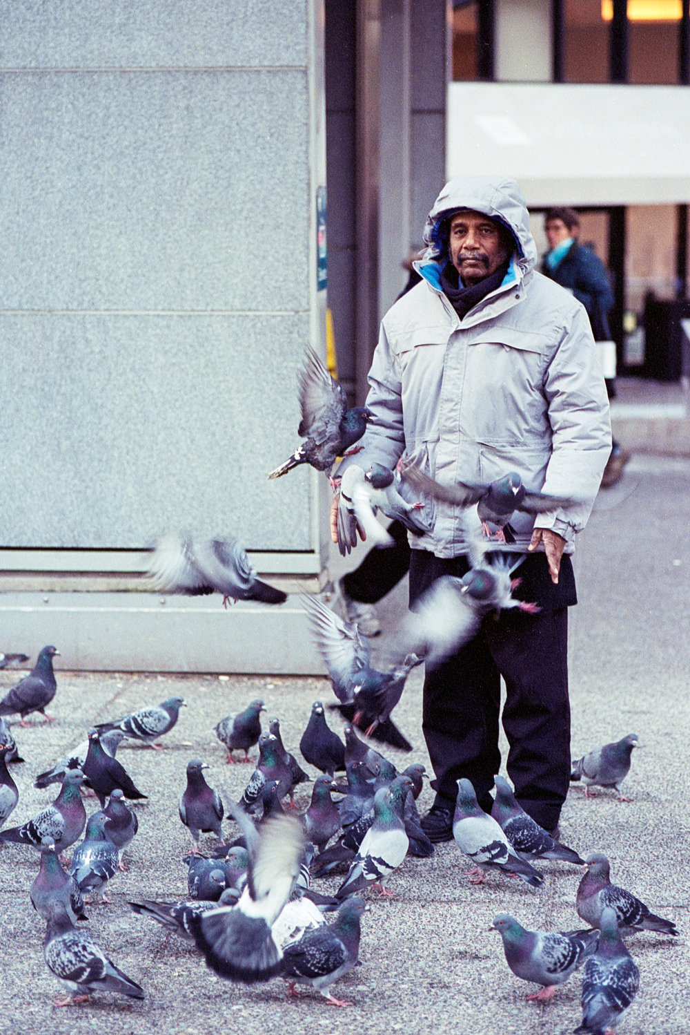 Another man feeding the pigeons next to Vancouver City Centre station