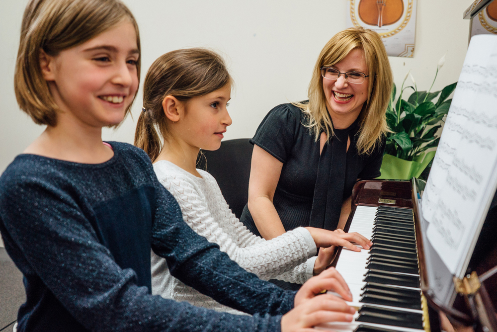 Girls having fun learning piano