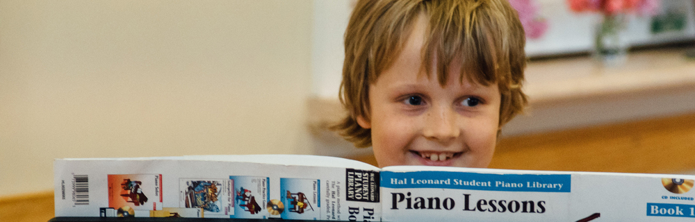 Boy enjoys performing piano at a concert