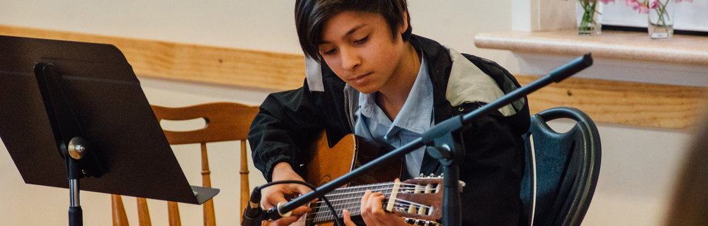 Boy performs guitar at a student concert