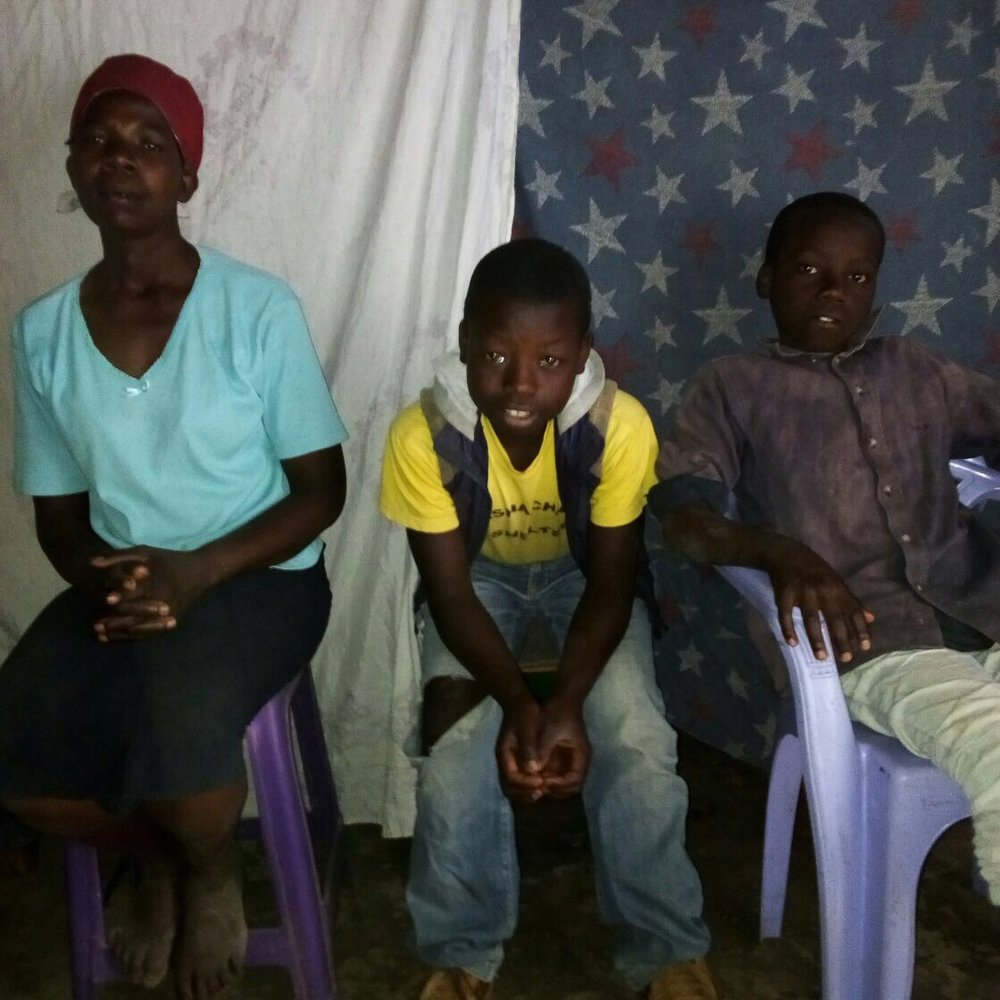 Fidel (far right) and his brother Emmanuel were reunited with their mother this month. Both boys will be beginning school in January.