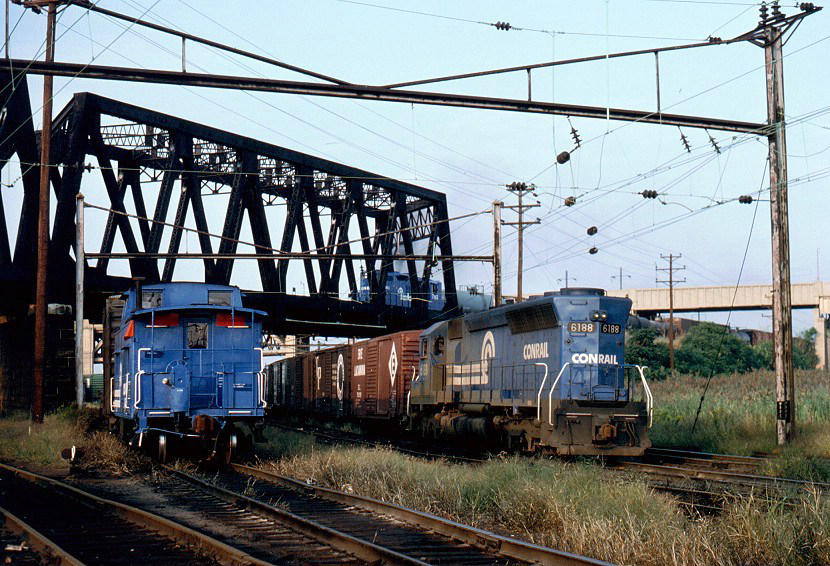 September 17, 1977 found freshly painted CR No. 18886 on the rear of a freight on the Northeast Corridor in Newark, NJ. The former Lehigh Valley Railroad mainline soars overhead in this busy scene.  (Vincent J. Benkovitz photo, Brian Woodruff collection)