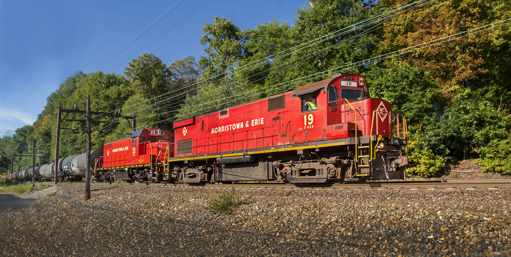 No. 19 is the sole power for this interesting consist rolling through Mt. Tabor, NJ on September 17, 2015. In tow is recently repainted M&E No. 23 and Tri-State's four cabooses, all bound for the URHS yard in Boonton, NJ.  (Bill Bossert photo)
