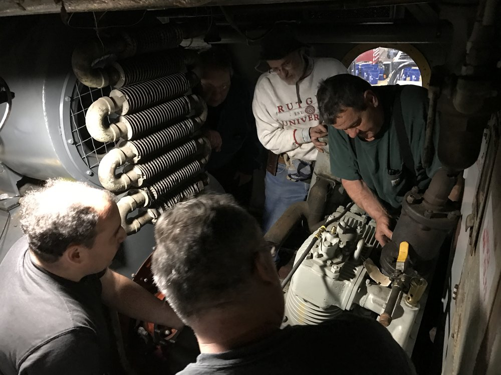 Volunteers and mechanics muscle the new compressor into place.