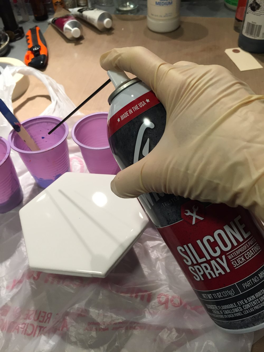 Give your prepared cups a squirt of silicone.  You do not need to add silicone to every color.  Experiment and decide what outcome you want to achieve. Mix silicone ONLY slightly into your paint mix (I make an X with my stirring stick).