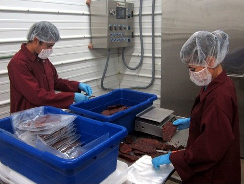 Fede (left) packaging jerky as part of his job at PCLM.