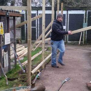 Volunteer Peter makes a valiant attempt to find the  pole vault as he specs out the design of the new barriers