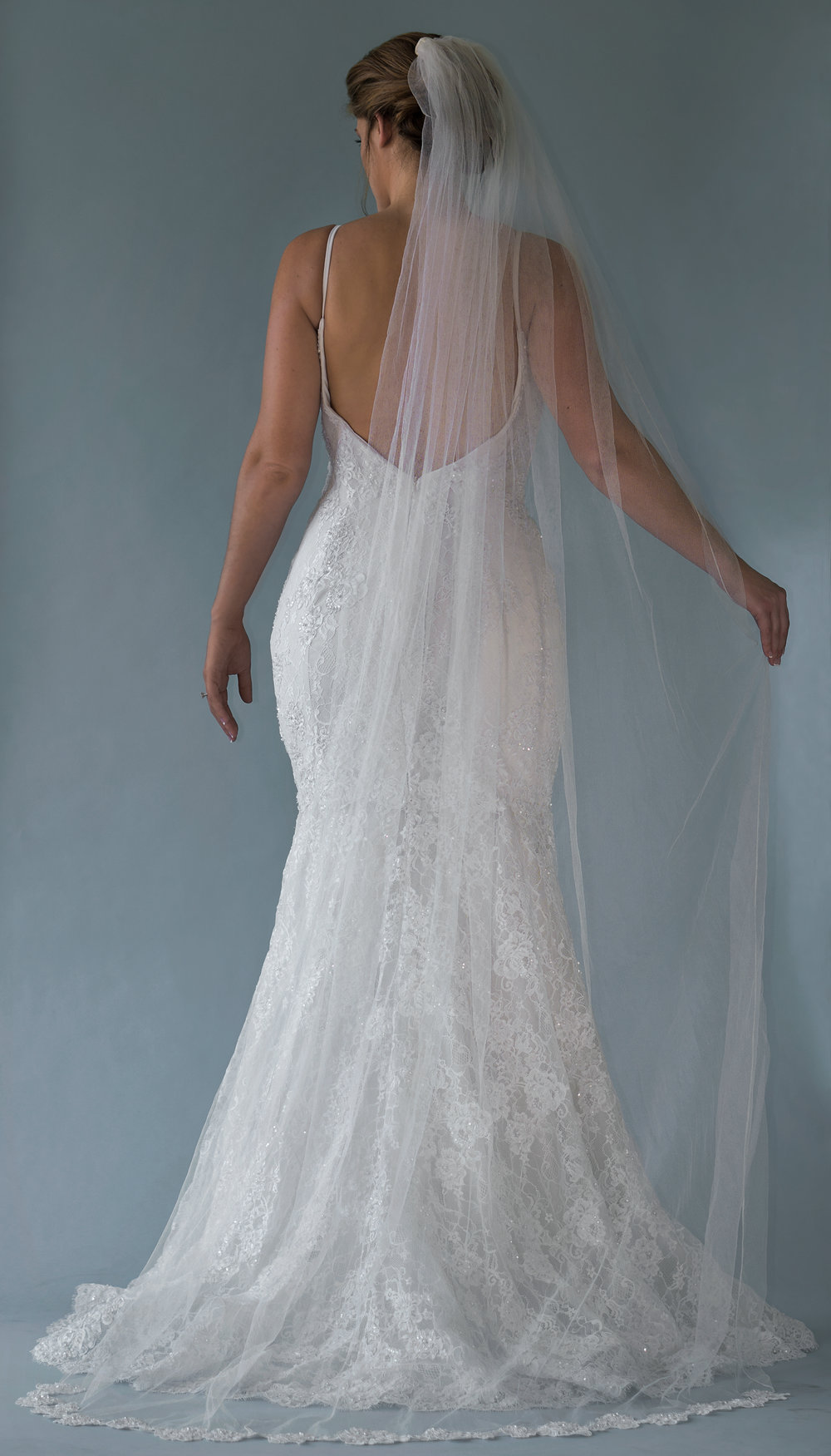 Stella Gown - From the Fall 2018 Collection - Plunging V-neck lace bodice with illusion insert and thin straps. Form fitting and sitting very low on the back. Mermaid style with wide horsehair for structure. Invisible zipper closure.Each dress is made by hand in the USA by our designers.  Shown here with our Cathedral length silk veil edged along the end with coordinating Alencon lace.