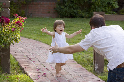 Little girl running to dad's open arms