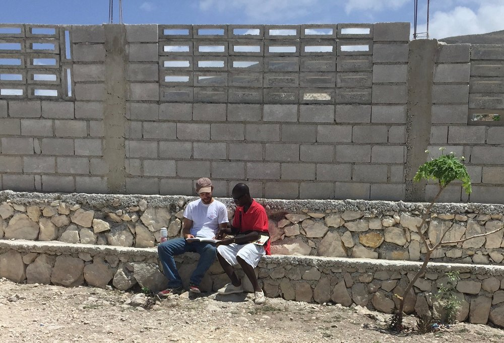 Michael sharing his faith with a young man in Haiti.