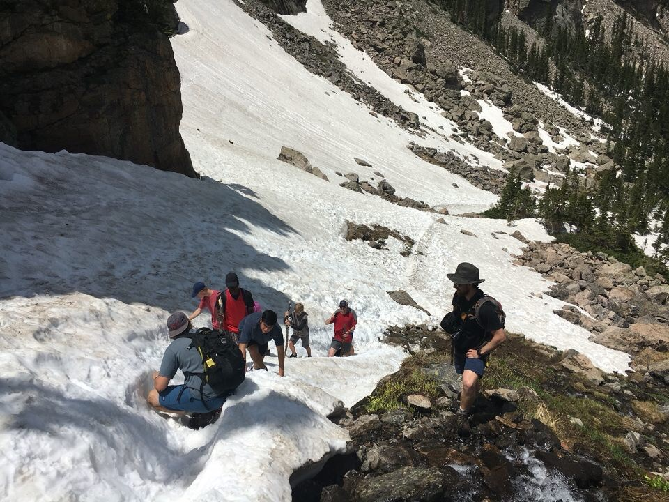 Davis & Patrick guiding kids across a snow field up to an incredible mountain waterfall.