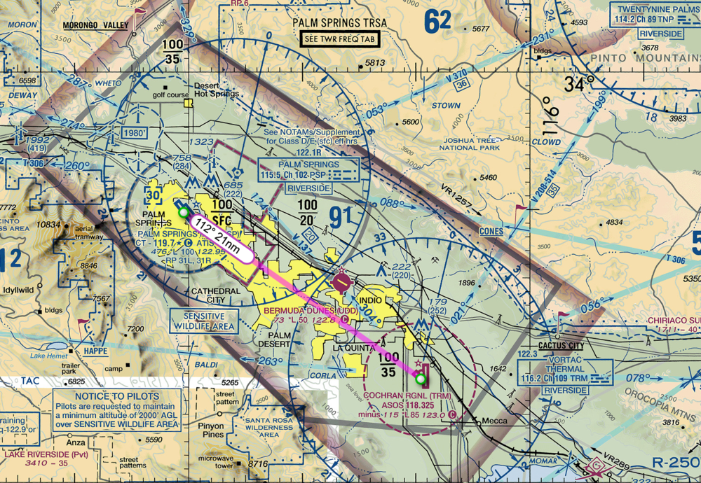 Palm Springs on the left with a blue ring around it.. The ring is actually dashed, signifying that it is in Class D airspace (the ring looks solid because it overlays another color). Jacqueline Cochran is on the right, surrounded by a dashed magenta ring, indicating Class E airspace. The entire area is surrounded by both a shaded magenta block and also a gray line, indicating Class E airspace and also a TRSA (terminal radar service area). The TRSA will unknowingly come into play in my flight. Confusing, yes.