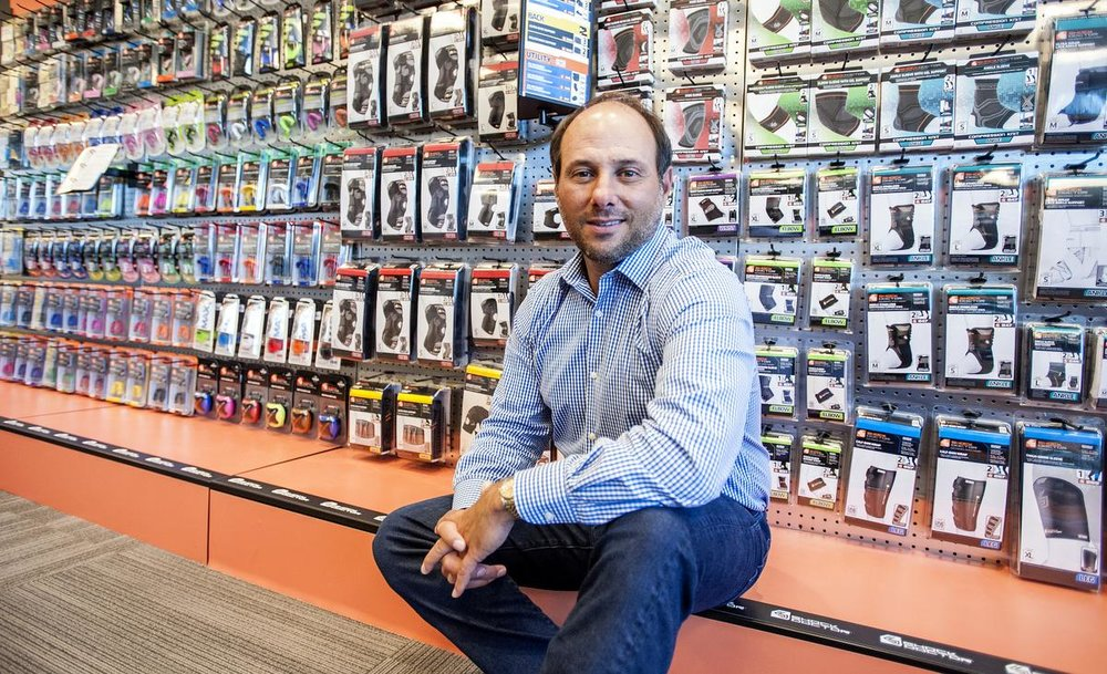 Tony Armand, CEO of United Sports Brands, stands in the lobby of the compnay's co-headquarters and 120,000-square-foot distribution center in Fountain Valley.