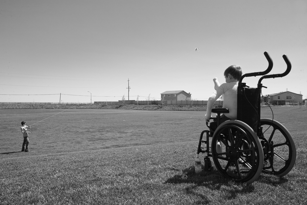 Apr. 16, 2009 - Newman, California, USA - Garrett Spaulding, 12, born with Epidermolysis watchesfrom his wheel chair as his brother David flies a kite on a windy afternoon. Garrett doesn't have the strength to control the kite himself in a strong wind, nor does he like the feel of it in his hands. (Credit Image: Andre J. Hermann/ZUMA Press)
