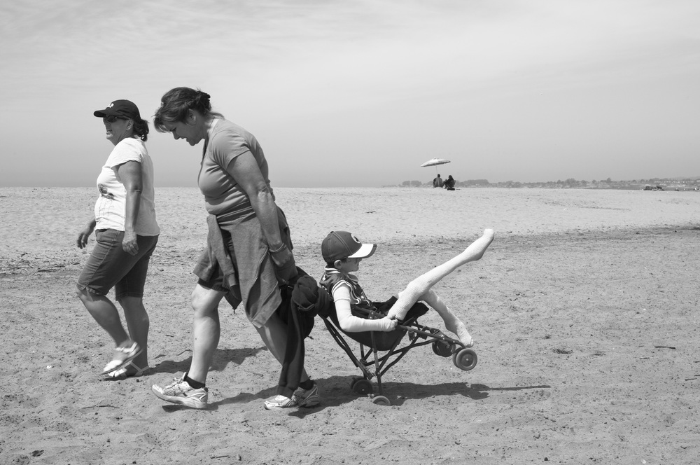 "May 11, 2009 - Santa Cruz, California, USA - Lorraine Spaulding, pulls Garrett across the hot sand in a stroller to meet the rest of his class during a class field trip to the beach. Lorraine admits that ther life changed drastically after having Garrett who was born with Epidermolysis Bullosa. ""Going places and doing things became a little more challenging."""